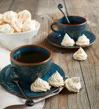 Meringue cookies and two cups of tea. Selective focus