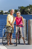 Happy Senior Couple on Bicycles By a River or Sea