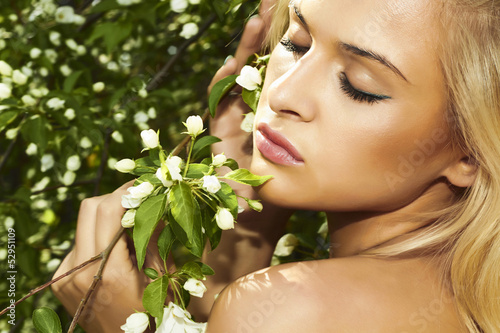 portrait of beautiful blond woman with apple tree. summer