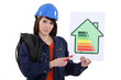 Female electrician holding screwdriver and energy poster