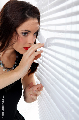 Woman peering through venetian blinds