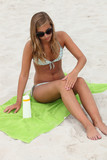 Young woman applying sunblock at the beach