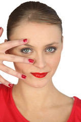 Woman spreading her fingers over her face