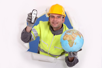 happy-looking builder holding globe and cordless phone
