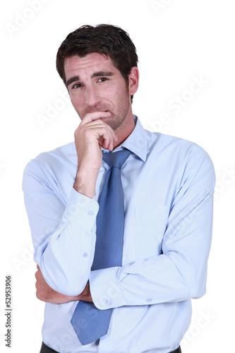Pensive businessman rubbing chin