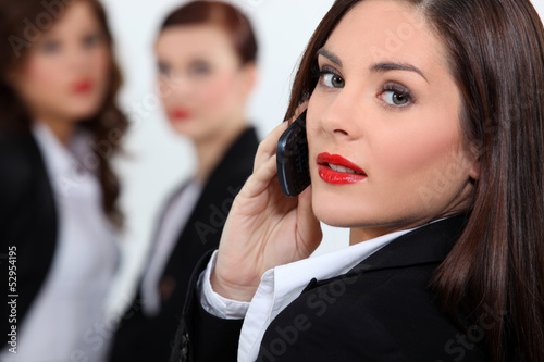 Businesswoman in red lipstick using a cellphone