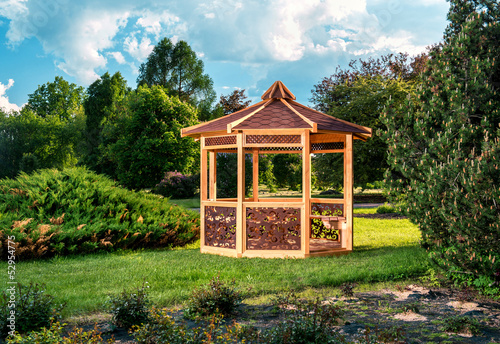 Papiers peints Jardin Outdoor wooden gazebo over summer landscape background