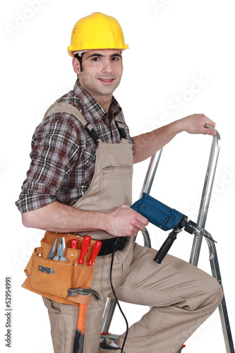 Laborer with drill on a ladder