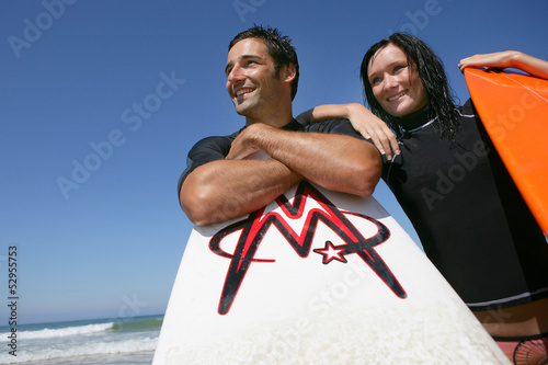 Couple stood on beach with their surfboards