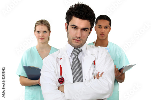 young doctor standing cross-armed with colleagues nurses