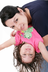 Mother playing with her daughter and holding her upside down