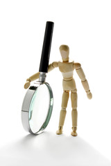 Wooden mannequin holding magnifying glass