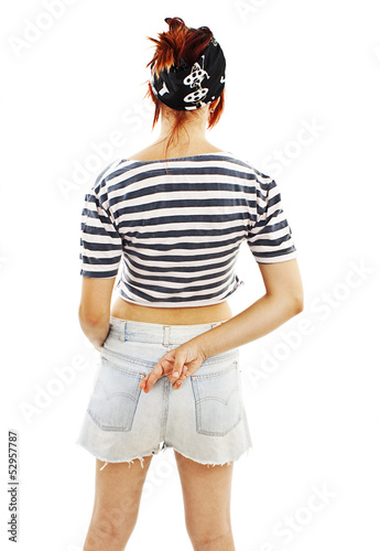 Young woman with fingers crossed behind back