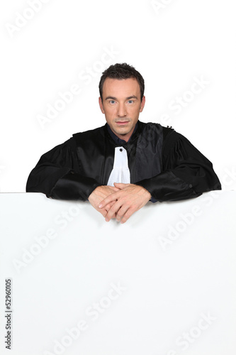 Man in graduation robe holding blank board