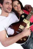 Young man with a guitar and a pretty girl