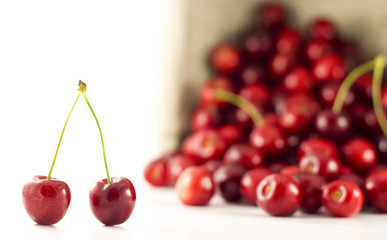 A pair of cherries with spilled cherries in the background