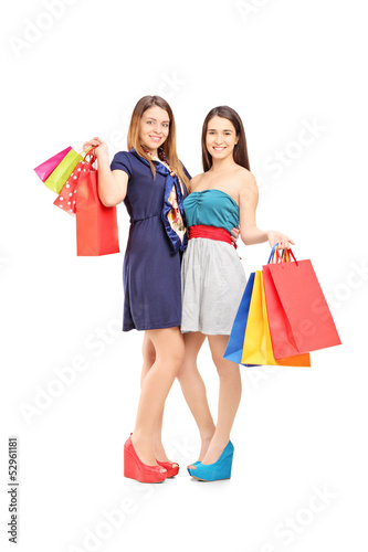 Full length portrait of two female friends holding shopping bags
