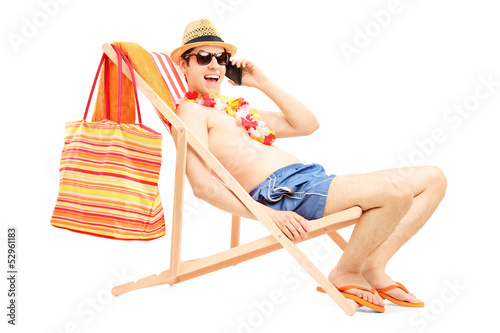 Man enjoying on a sun lounger while talking on a mobile phone