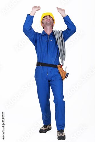 A construction worker raising his hands.