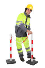 Construction worker putting up a barrier