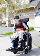 Happy little disabled boy in wheelchair