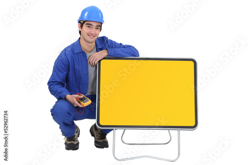 An electrician kneeled next to a blank road sign.