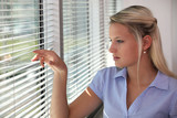 Blond office worker peering through window blinds