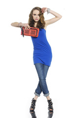Full body young woman in shirt and purse posing at studio