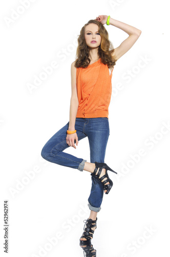 Full body young woman in shirt and jeans posing at studio