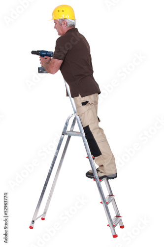 Senior carpenter stood up ladder with drill