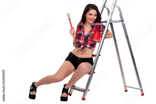 Sexy woman sat on ladder holding paint pot