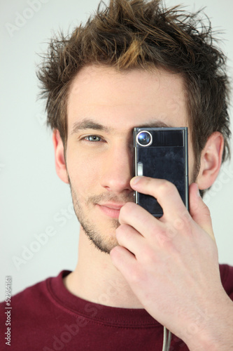 Man covering his eye with a camera
