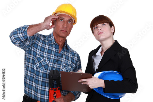Tradesman and engineer looking at the ceiling
