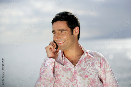 Smiling man on the phone by the coast