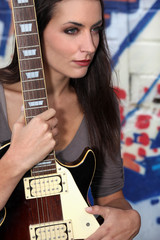 young woman holding a guitar