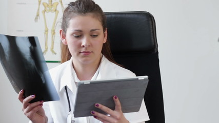 Female doctor with tablet computer looking at xray picture