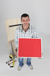 Carpenter holding up picture frame