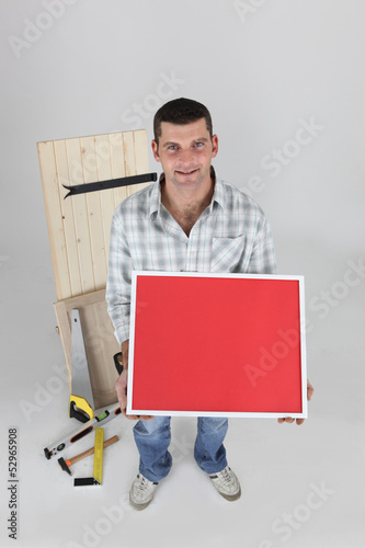 Carpenter holding up picture frame
