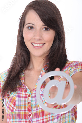 Young woman holding an @ sign