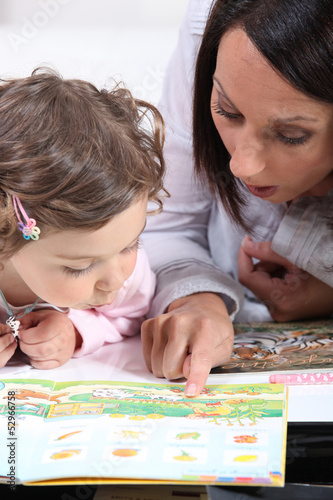 Mother teaching daughter to read