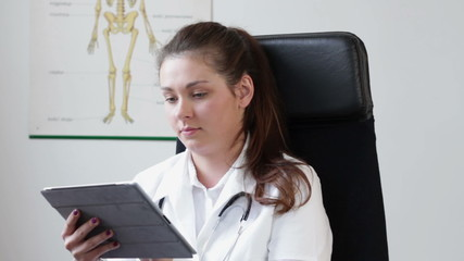 Female doctor with tablet computer in her office, tracking shot