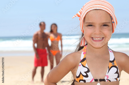 Young girl at the beach with her parents