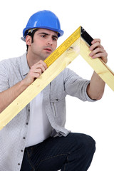 carpenter measuring a wooden frame