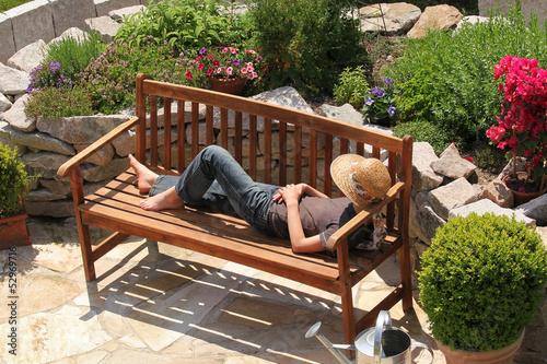 Leinwandbild Motiv Relaxing on a garden bench