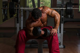 shirtless bodybuilder doing heavy weight exercise for biceps
