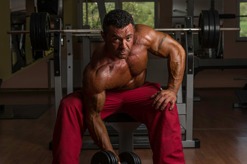 shirtless body builder doing heavy weight exercise for biceps