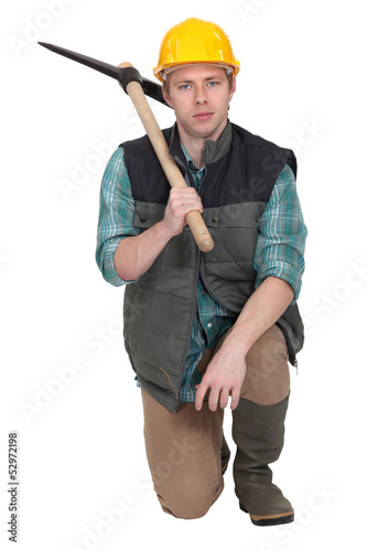 Man with pick-ax knelt on one knee