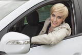 smiling blond girl with short hair sitting in her new car