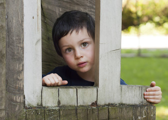 Child in  wooden window of  playhouse in playground