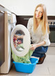 Happy long-haired woman loading clothes into  washing machine